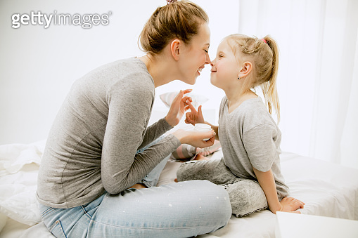Young mother and her little daughter hugging and kissing on bed