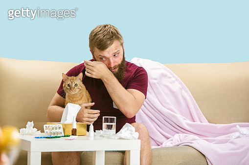 Young man suffering from allergy to cat hair