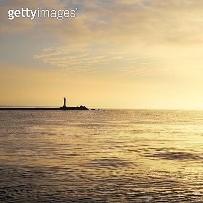 Horizontal image of a distant lighthouse silhouette on a stone pier on daugava river in Riga at sunset