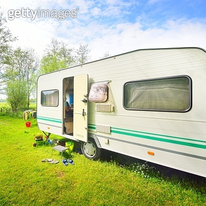Caravan trailer camping on a green lawn under a tree in springtime