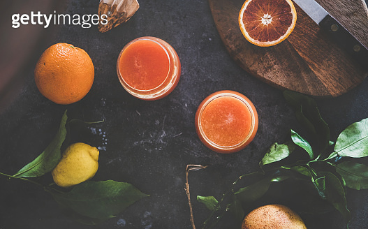 Flat-lay of orange juice in glasses and fresh citrus fruits