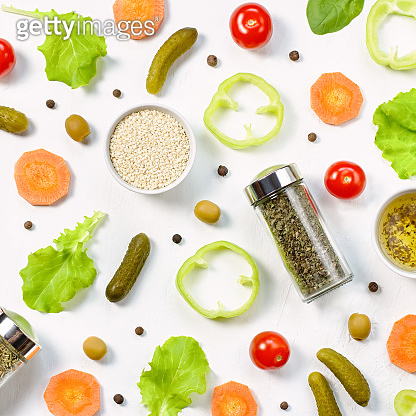 Salad ingredients layout on white desk. Food pattern with cherry tomatoes, cucumbers, greens, pepper and spices