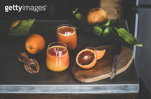 Two glasses of blood orange juice or smoothie and fruits