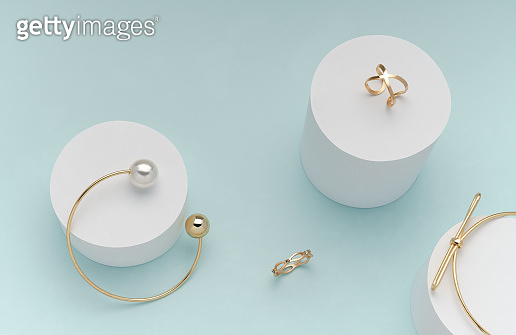 flat lay of golden bracelets and rings on on white cylinders on bright pastel color background