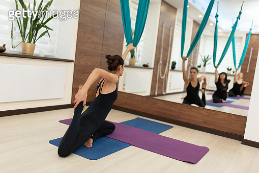 Woman doing fly yoga stretching exercises in gym. Fit and wellness lifestyle