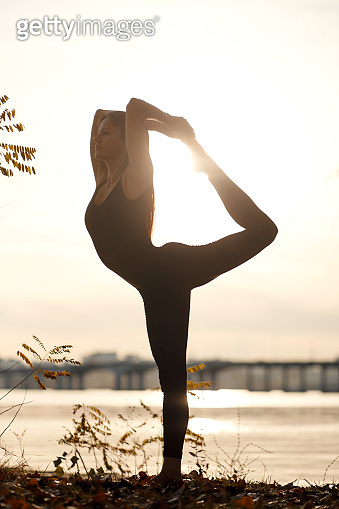 Young woman practicing yoga exercise at river beach and city background.