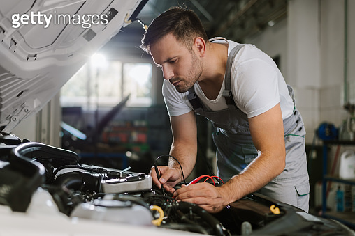 Mechanic working with car diagnostic tool in a workshop