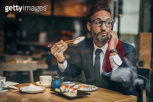 Man in the sushi restaurant using phone