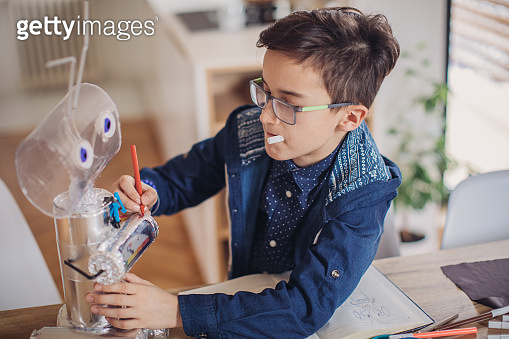 Boy engineer making a robot for school