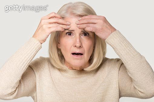 Mature woman feels upset about facial wrinkles studio conceptual image