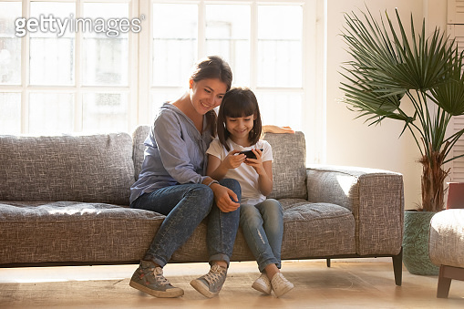 Happy mom and kid daughter using smartphone sitting on couch