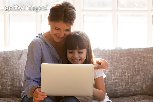 Happy mom with little daughter having fun online with laptop