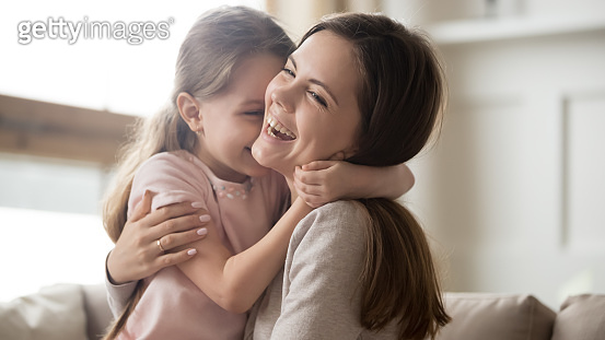 Loving young mother laughing embracing smiling cute funny kid girl