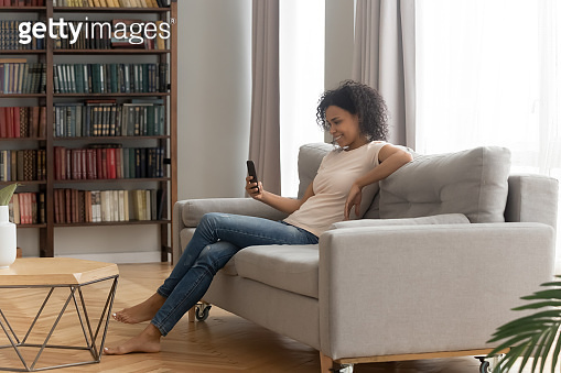 Happy young african american woman using smartphone sit on sofa