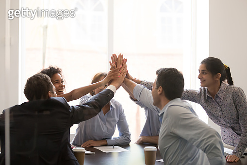 Excited multi racial businesspeople celebrating corporate success giving high five
