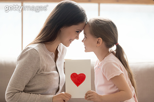 Happy mom and kid daughter holding greeting card with heart