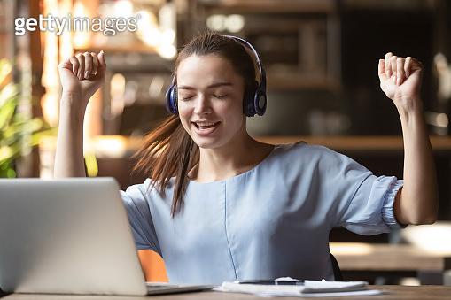Excited woman wearing headset enjoying music, using laptop in cafe