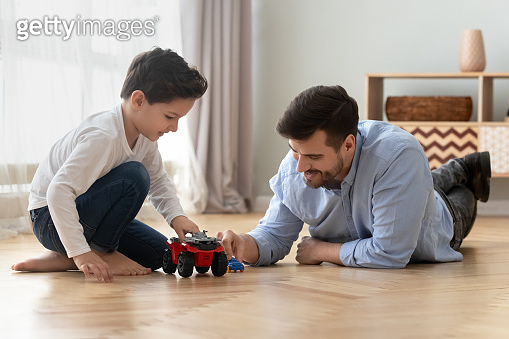 Father and little son playing toy cars on warm floor
