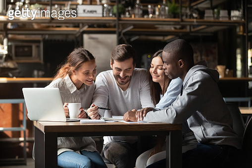 Happy diverse people working with paper documents in cafe together