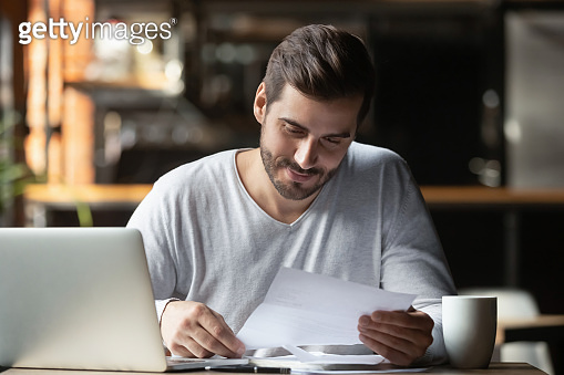 Satisfied man doing paperwork in cafe, holding letter or legal document