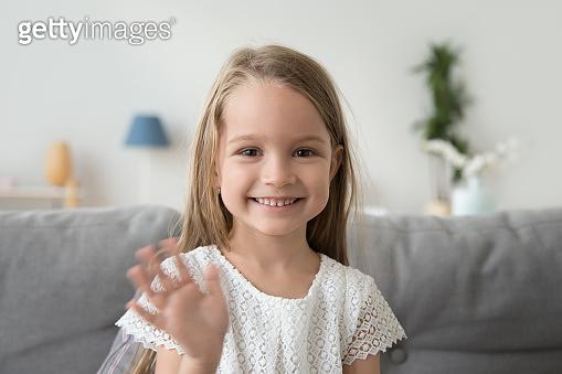 Smiling little girl looking at camera, waving hand, greeting