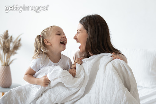 Happy mother laughing with kid daughter holding duvet in bed