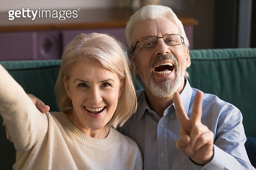 Smiling funny older couple take selfie, phone cam view