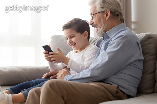 Excited grandparent and grandson play game on smartphone together
