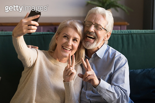 Happy funny mature senior couple taking selfie looking at smartphone
