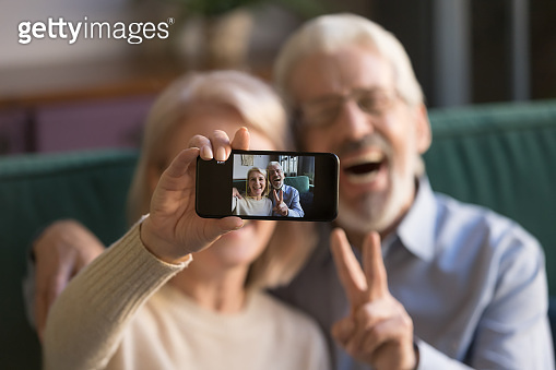 Happy old couple taking selfie on cellphone, focus on display