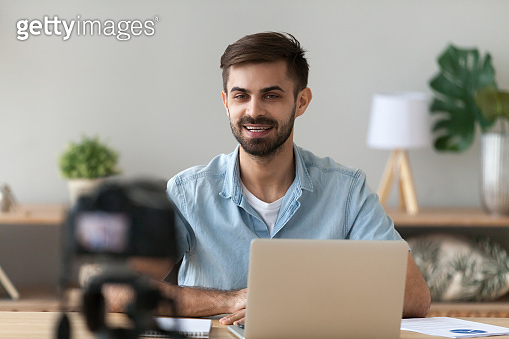 Young confident man speaker talking on digital camera recording vlog