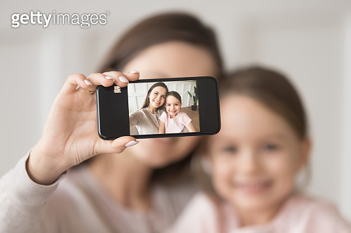 Happy mother holding phone taking selfie on cellphone with daughter