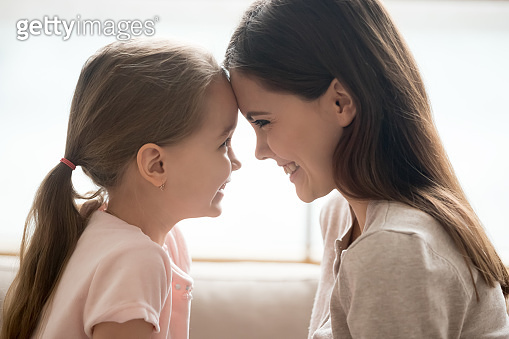 Happy kid girl and smiling mother touching foreheads, side view