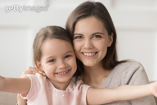 Headshot of happy family mother and kid daughter embracing bonding