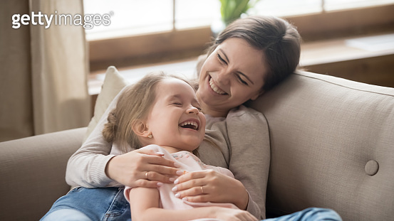 Happy mom embracing kid daughter laughing together lying on couch
