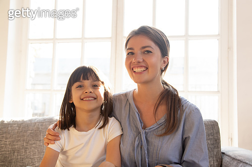 Happy mom embracing little kid daughter looking at camera webcam