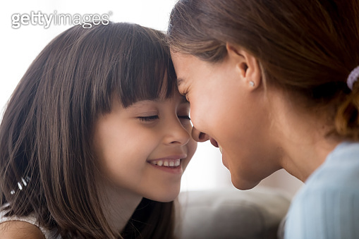 Smiling little child girl tenderly touching foreheads with happy mom
