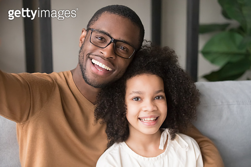 Smiling black father and child taking selfie looking at camera