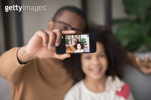 Happy african dad taking selfie with kid daughter on cellphone