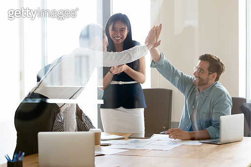 Happy successful business men giving high five at team meeting