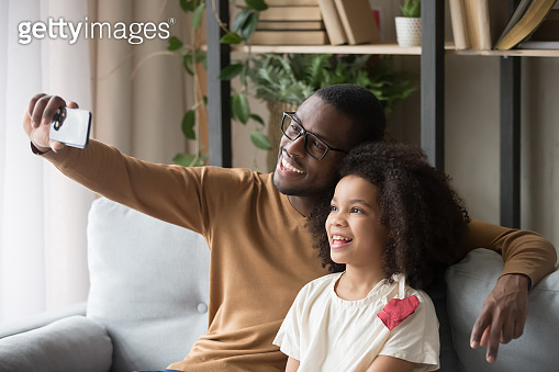 Smiling african family dad and daughter make selfie photo