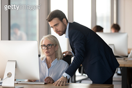 Serious male mentor supervising female employee helping with computer problem
