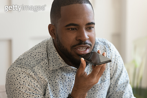 Young african man holding phone ask voice assistant make call