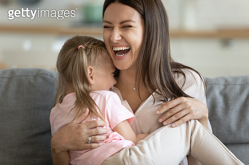 Cheerful young mom laughing playing with cute small child daughter