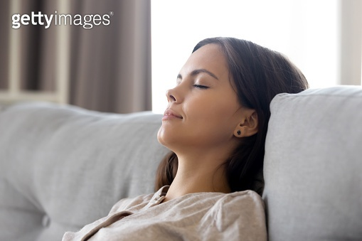Serene calm woman relaxing leaning on comfortable couch having nap