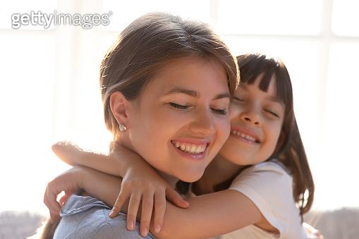 Loving mom and little daughter hug enjoying tenderness