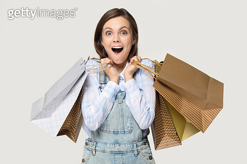 Shopper girl holding heaps of shopping bags isolated on grey