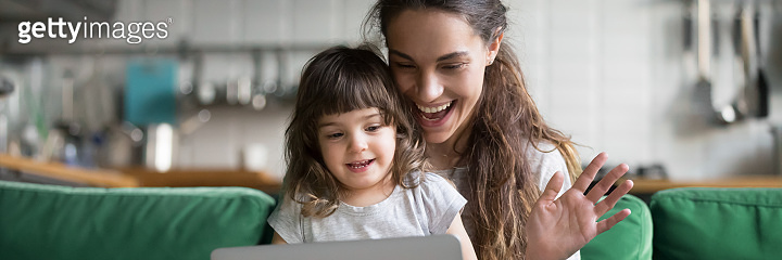 Mother and daughter waving hands looking at camera using computer