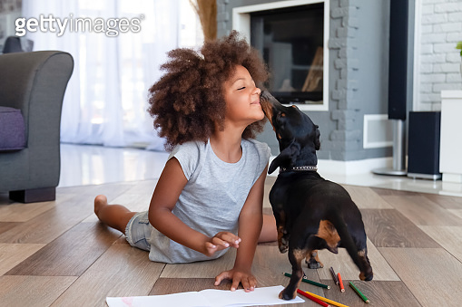 Cute little girl lying on floor playing with dog