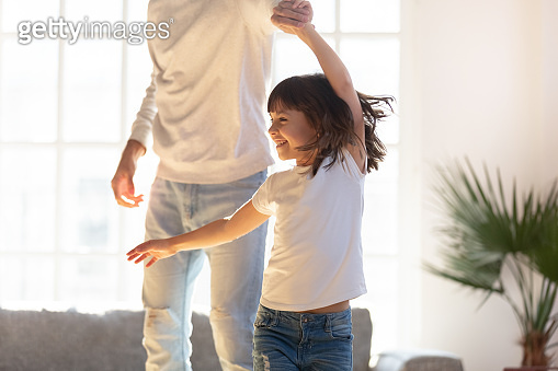 Close up loving father and little daughter dancing at home